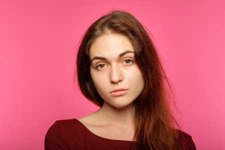 young beautiful girl with a poker face. lack of emotion. portrait of indifferent cold icy nonchalant woman on pink background. Reklamní fotografie