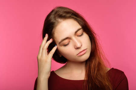 tired sad young woman. portrait of a sleepy drowsy and exhausted pretty girl on pink background. Stock Photo