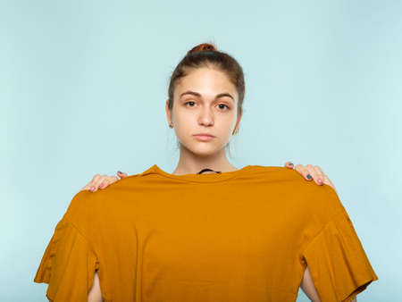 body weight issues. young beautiful girl holding a big size t-shirt as if she is fat. public opinion and distorted self image.