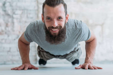 plank hold. smiling man training. strength and power exercising. athletic lifestyle. Фото со стока