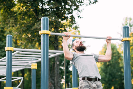 sport fitness and outdoor training. man doing pull ups on bar. chest muscles and biceps workout. Фото со стока