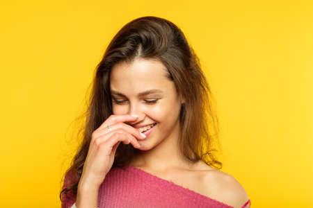 happy smiling joyful delighted woman. young beautiful brown haired girl emotional portrait on yellow background. facial expression. Stock Photo