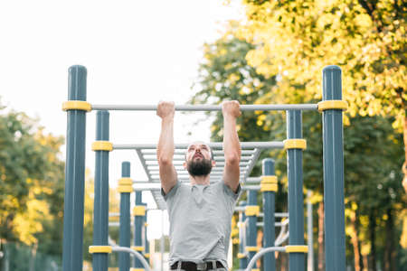 workout and exercise. man doing pull ups. athletic lifestyle and training.