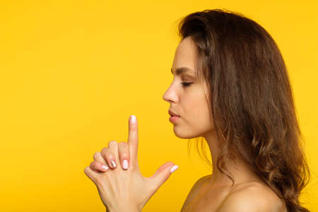 female spy or undercover agent. serious woman with a finger gun. concept of confident purposeful determined girl. side view portrait on yellow background.