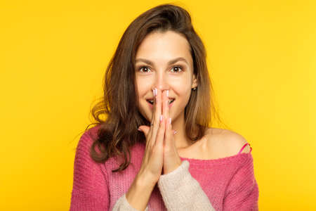 emotion face. overwhelmed perplexed shocked surprised astounded woman. young beautiful brown haired girl portrait on yellow background. Stock Photo