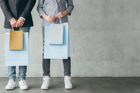 shopping store discounts and sale concept. cropped image of casual couple holding bags with goods. Stock Photo