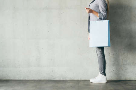 sale and shopping. woman holding paper bag. copyspace on grey background.