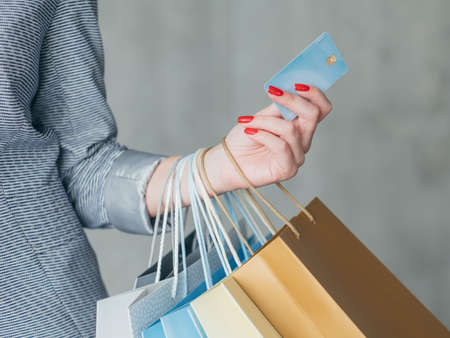 money loan for shopping. woman holding credit card and multiple bags in her hand.