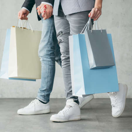 shopping for holiday gifts. cropped image of casual couple walking holding bags with goods.
