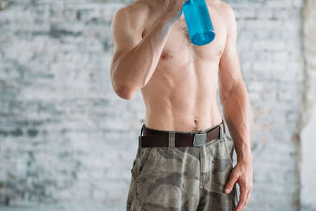 muscled male torso. sport and training. fit athletic bare chested man drinking from a water bottle.