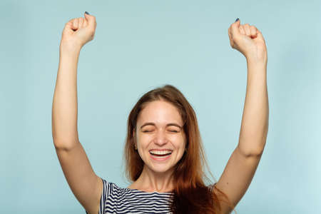emotion expression. very happy joyful thrilled to bits woman with beaming smile and hands in the air. young beautiful brown haired girl portrait on blue background. Stock Photo