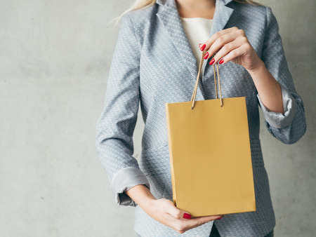 brown paper bag in woman hands. presents shopping concept.