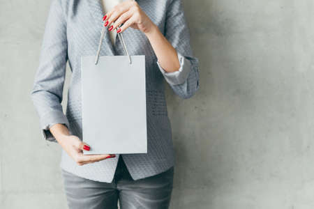 its shopping time. woman holding white paper bag in hands. store sale concept.