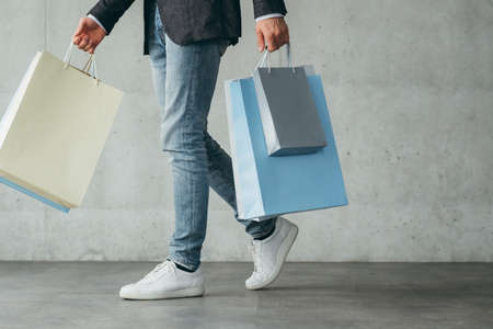 shopping therapy for males. casual guy walking holding lots of bags with goods.