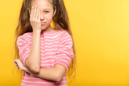 eyesight check. girl covering one eye with hand. ophthalmology concept. Reklamní fotografie