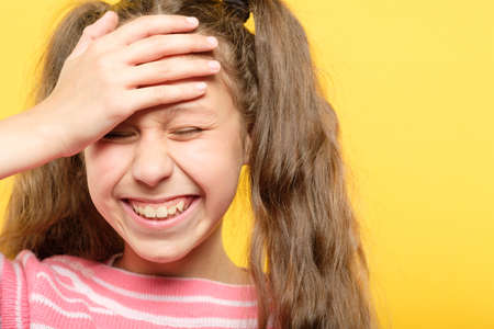 laughing girl embarrassed with her silliness cover forehead with hand. facepalm failure and shame concept.