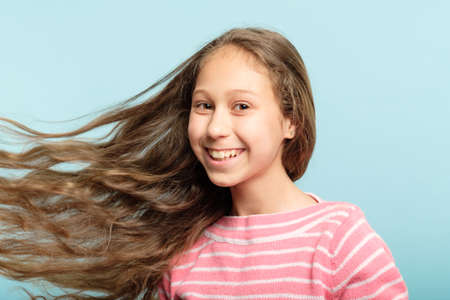 adolescent girl with wavy hair flying in the wind on blue background. haircare for kids.