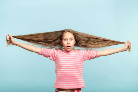 haircare and styling for kids. shocked adolescent girl holding her long wavy hair. 스톡 콘텐츠