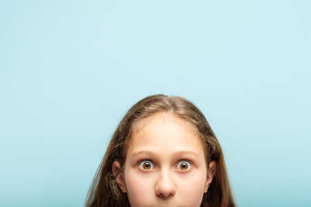 startled surprised shocked girl peeking out from the bottom of blue background. emotion and facial expression concept.