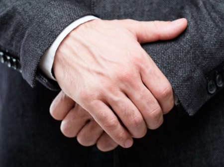 man hands clenched in front. gesture of protection defence and insecurity. holding oneself by the hand.