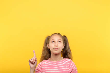 look above. girl pointing up with index finger to a virtual object or text. empty space for advertisement.