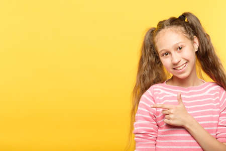look left. smiling girl pointing her index finger to a virtual object. empty space for text placement.