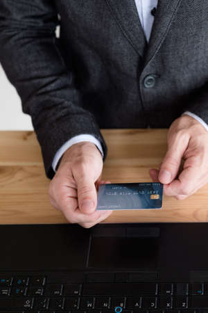 man holding credit card above laptop. online banking concept.