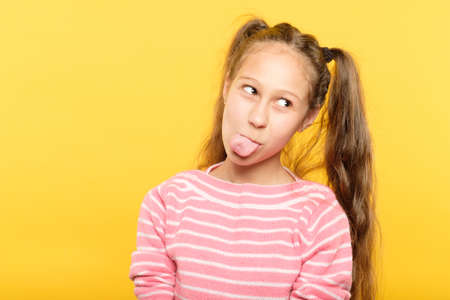 naughty girl on yellow background sticking her tongue out. frolicking and childish behavior.