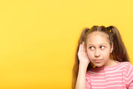 little girl eavesdropping. listening to hear secrets or gossip. child curiosity and pry. Stock Photo