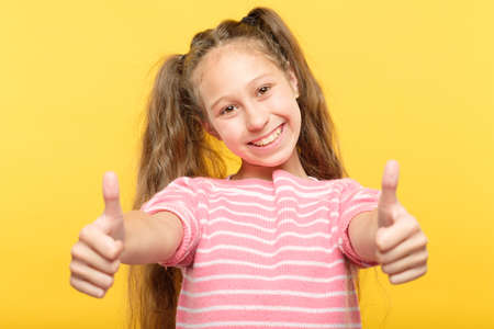 smiling child showing two thumbs up. success and approval concept. Stock Photo