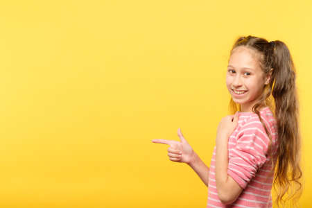 look left. smiling girl pointing her index finger to a virtual object. copy space for advertising .