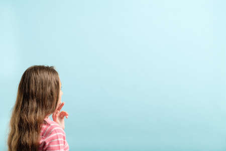 backview of a girl looking at invisible virtual object on blue background. empty space for product placement.