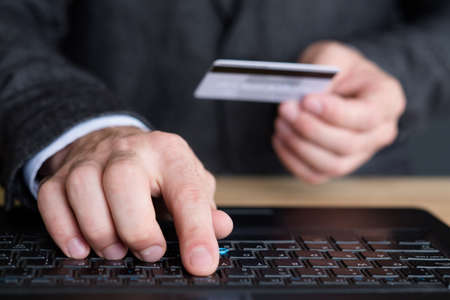 man hands holding bank card and typing on laptop. online banking account login. Stock fotó
