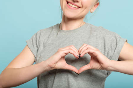 smiling woman making a heart shape with her hands. love and feelings expression.