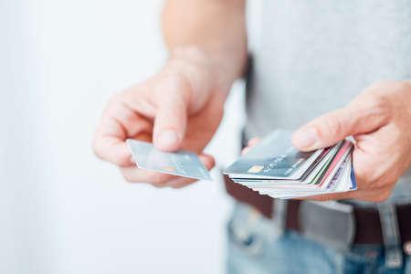 sconto shopping o carte fedeltà. moderna attività di marketing. uomo che tiene una selezione di carte di plastica.