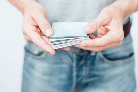 credit card online operations and banking. money management and finances. man holding assortment of plastic cards.