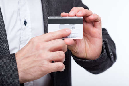 credit card CVV2 code. online payments security. man holding plastic card and pointing to number.