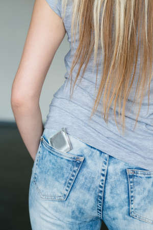 std protection. condom as means of birth control. backview of a woman with a contraceptive in her jeans pocket