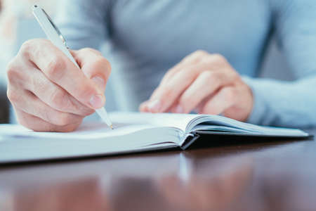 man hand writing in day planner. work schedule and personal organizer concept. Stockfoto - 111517423
