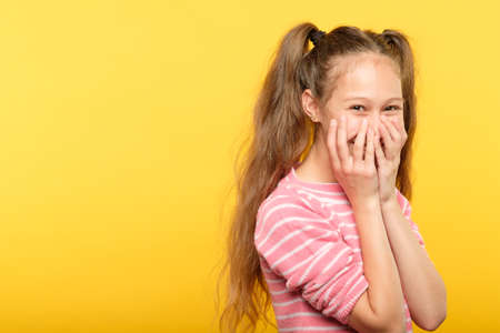 shy smiling embarrassed girl covering mouth with hands. young cute child emotional portrait on yellow background. Stock Photo