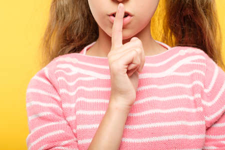 girl with finger on lips. naughty child secret and conspiracy. cropped shot.