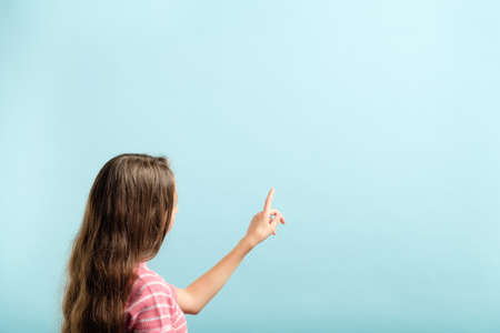 girl using index finger to press invisible button on blue background. interface or virtual screen concept. empty space.