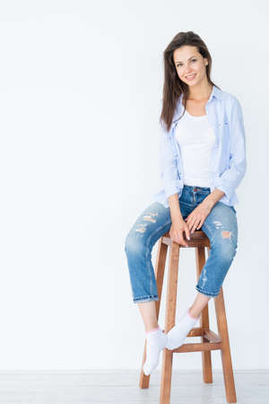 smiling woman sitting on wooden stool on white background. casual lifestyle. Banque d'images