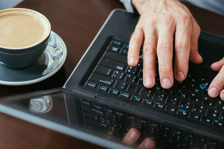 coffee break and work. man hands typing on laptop. cup of latte on the table.