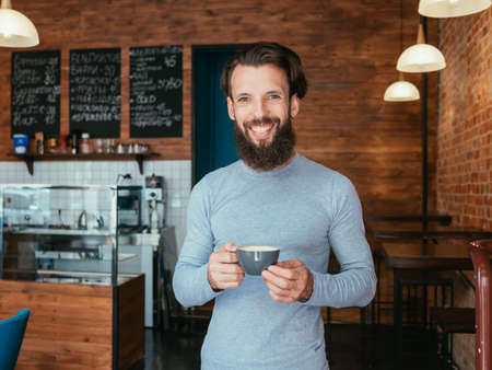 man standing in coffee shop holding cup of cappuccino. casual business owner.