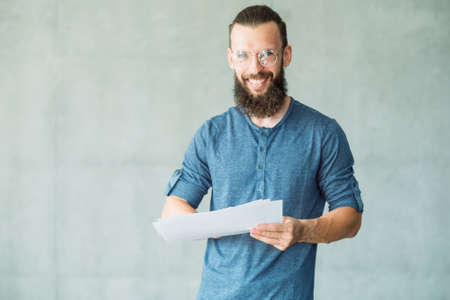 smiling man holding papers. information studying and business statistics. Banco de Imagens