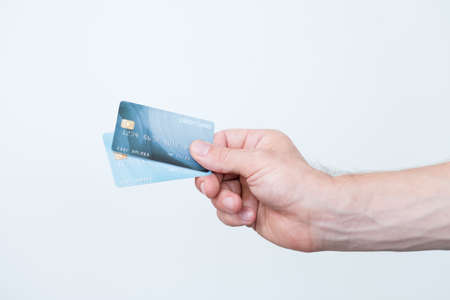 credit card online payments. personal finances and money management. hand holding bank card on white background. Stock Photo
