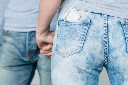 safe sex. condom as a pregnancy prevention. backview of a woman with a contraceptive in her jeans pocket
