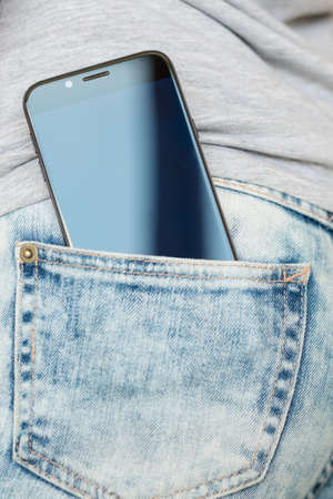 mobile devices addiction. social networks concept. phone in woman back jeans pocket Banque d'images - 112696577