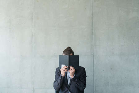 business man covering face with notebook. bookworm knowledge reading planning.